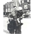 Max Stern in army uniform, Toronto, 1943. Ontario Jewish Archives, Blankenstein Family Heritage Centre, fonds 33, series 2, item 13.|This item is a photograph of Max Stern dressed in his army uniform, holding two children, Sheldon Glass and an unknown girl. They are standing in the street in front of Mandel's Creamery. Max Stern was stationed in Toronto.