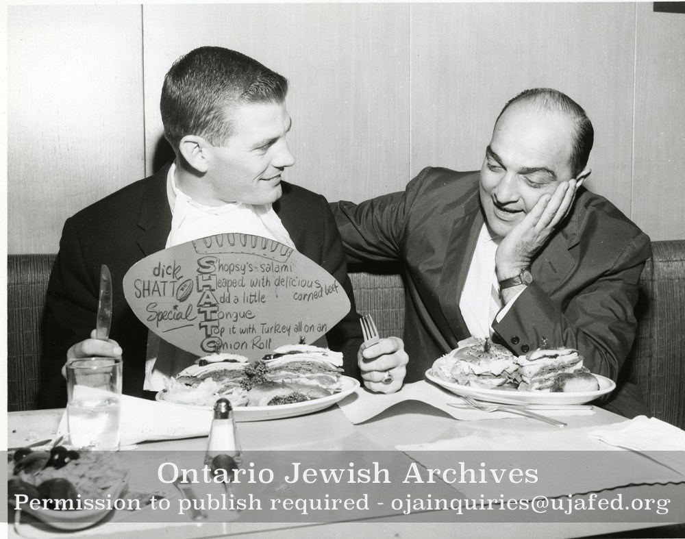 ... Canadian football player Dick Shatto and Lou Agasee at Shopsy's  Restaurant seated at a table with ...